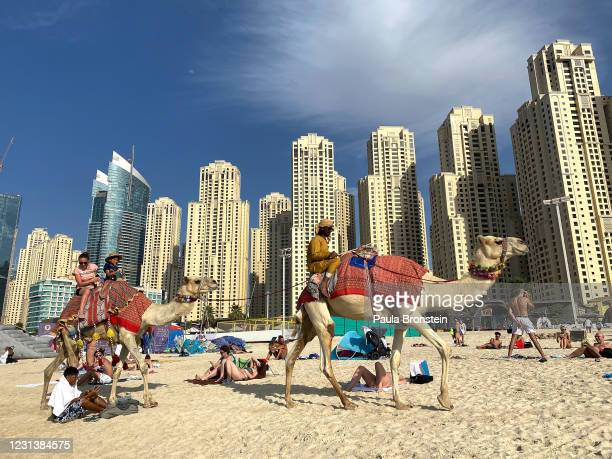 Tourists take a camel ride on Marina beach on February 22, 2021 in Dubai, United Arab Emirates. Dubai is open for business, excepting foreign...