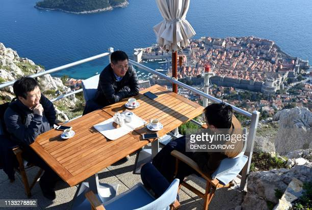 Tourists take a coffee on a terrace and enjoy the view from the Srd hill overlooking the old town in Dubrovnik Croatia on March 28 2019 Shepherding...