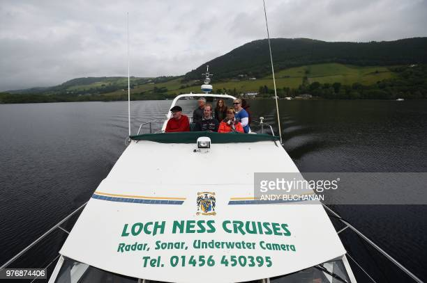 Tourists take a cruise aboard the 'Nessie Hunter' boat on Loch Ness in the Scottish Highlands Scotland on June 10 2018 Tales of a giant creature...