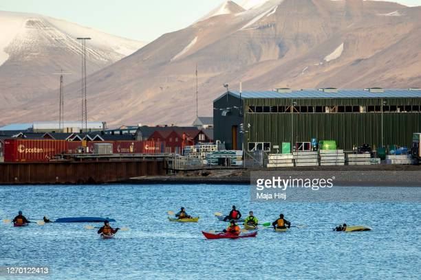 Tourists take a kayak trip on Svalbard archipelago on August 35 2020 near Longyearbyen Norway Longearbyen located far north of the Arctic Circle is...