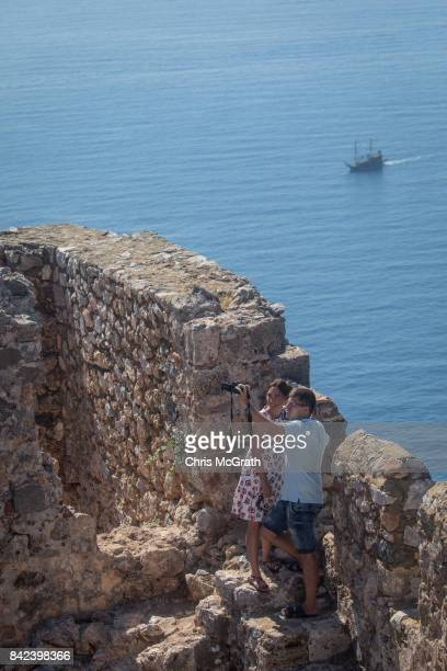 Tourists take a photo from the Alanya Castle on September 3 2017 in Alanya Turkey Turkey's tourism industry spiraled into crisis in 2016 after a year...