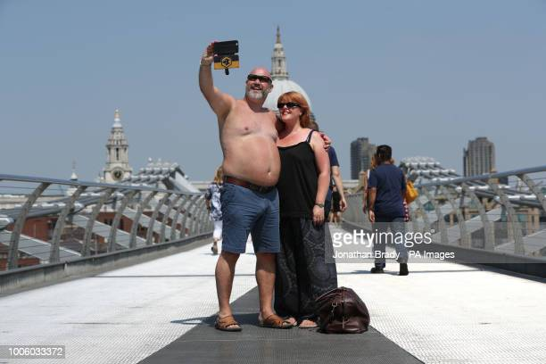 Tourists take a photo from the Millennium Bridge in London as the heatwave continues in parts of the UK with forecasted highs of 37C