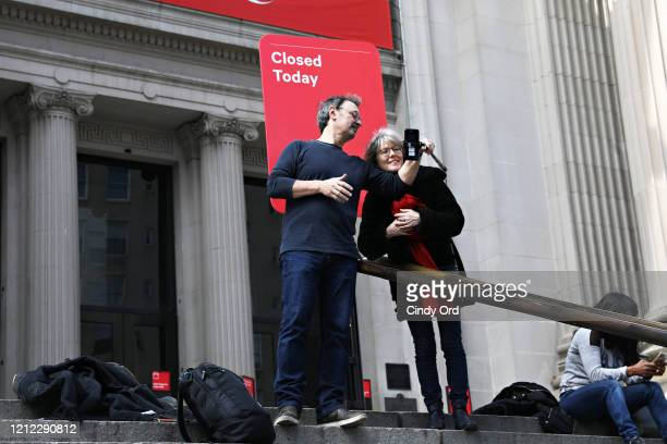 Tourists take a photo with a 'Closed Today' sign outside of The Metropolitan Museum of Art on March 13 2020 in New York City Due to the ongoing...