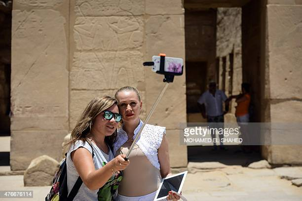 Tourists take a photo with a selfie stick as they visit Karnak temple in Luxor a town 700 kilometres south of the Egyptian capital Cairo on June 11...