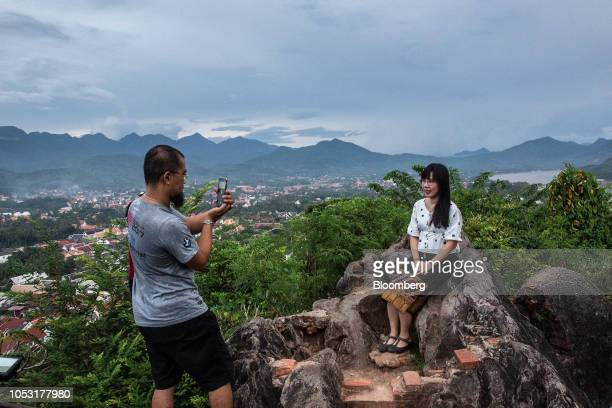 Tourists take a photograph at Mount Phousi in Luang Prabang Laos on Sunday Oct 21 2018 Laos's economy is set to expand at 7 percent this year...