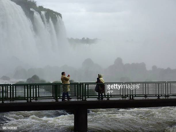 Tourists take a picture at a viewpoint on the Brazilian side of the Iguacu Falls on April 28 2010 The Falls declared a World Heritage Area by UNESCO...