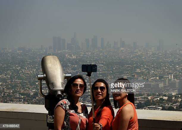 Tourists take a 'selfie' from the Griffith Observatory observation deck of the Los Angeles city skyline as heavy smog shrouds the city in California...