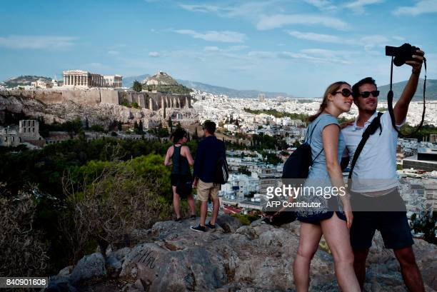 Tourists take a selfie in front of the Acropolis Hill in Athens on August 30 2017 / AFP PHOTO / LOUISA GOULIAMAKI
