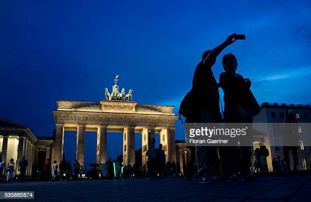Tourists take a selfie in front of the Brandenburg Gate on May 29 2016 in Berlin Germany