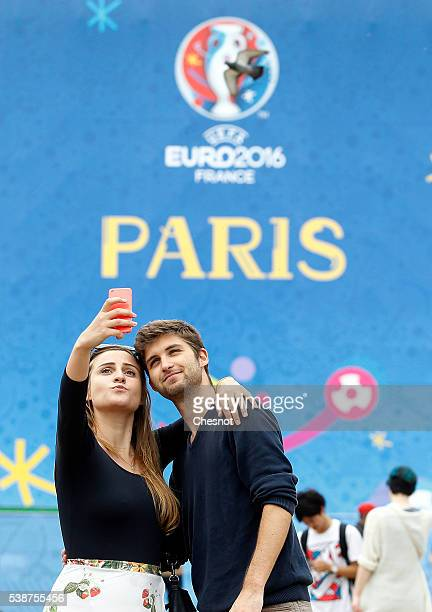 Tourists take a selfie in front of the fan zone decorated with posters for the the UEFA 2016 European Championship near the Eiffel Tower on June 08...