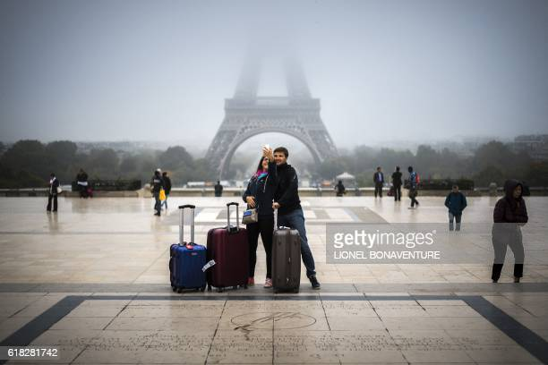 Tourists take a selfie on the Parvis des droits de l'homme square in front of the Eiffel tower on October 26 2016 in Paris / AFP / LIONEL BONAVENTURE