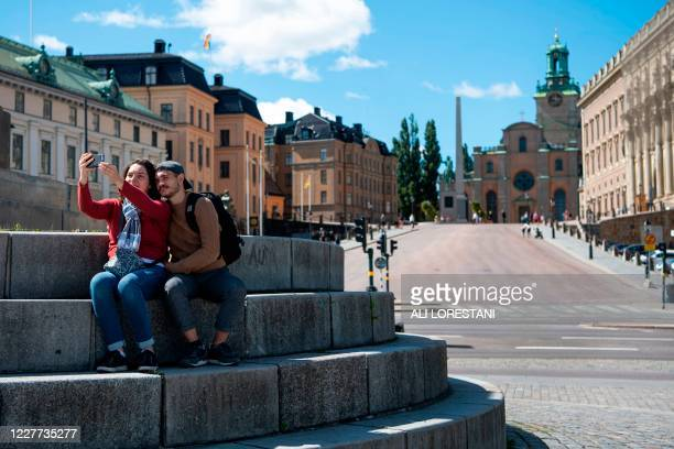 Tourists take a selfie outside the Royal palace in central Stockholm, Sweden on July 22, 2020. - The usually tourist-packed streets in the old town...