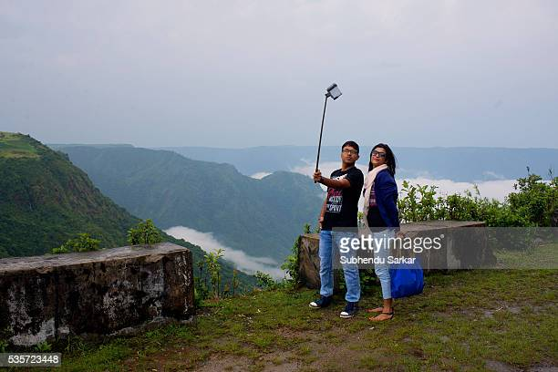 Tourists take a selfie photograph against a mountainous background in Shillong Meghalaya is a state in northeast India which means the abode of...
