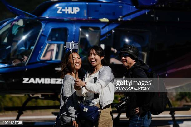 Tourists take a selfie picture on June 29 2018 after a helicopter flight over the Zambezi river in the resort town of Victoria Falls After nearly two...
