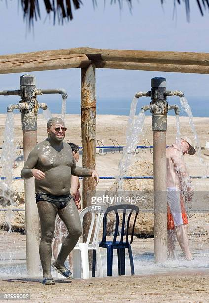 Tourists take a shower at the Ein Gedi Spa on the shores of the Dead Sea on September 10, 2008. As Israeli holidaymakers watch the Dead Sea...