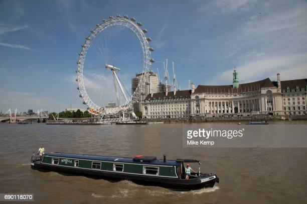 Tourists take a sightseeing tour cruise boat down the River Thames taking in some of the famous landmarks skylines and iconic buildings in the...