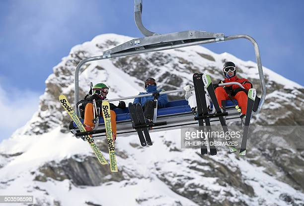 Tourists take a ski lift in the French ski resort of Val d'Isère in Central French Alps on January 6 after snowfall during the last few days / AFP /...
