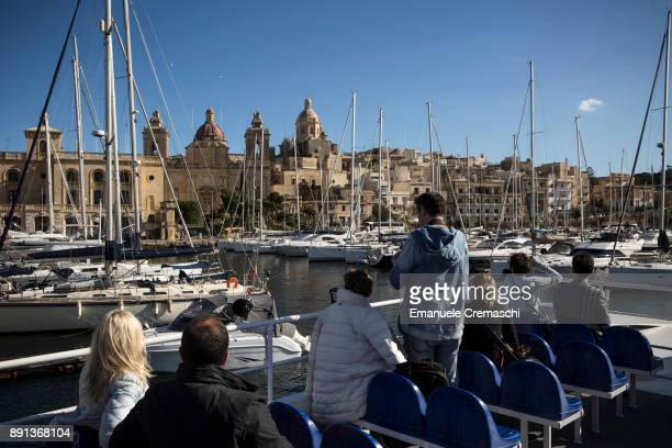 Tourists take a tour aboard a ferry sailing to the south side of Valletta's Grand Harbour on December 7 2017 in Vittoriosa Malta Valletta a fortified...