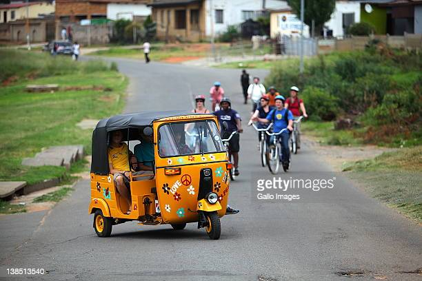Tourists take a township tour in a tuktuk February 6 2012 in Soweto South Africa Lebo Malepa owner of Lebo's Soweto Backpackers has created a unique...