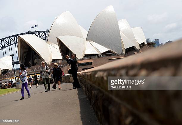 Tourists take a walk around Sydney's iconic Opera House on November 4 2014 Australia's central bank kept interest rates at a record low 25 percent...