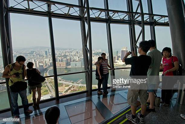 Tourists take in the view from the observation deck of the Macau Tower