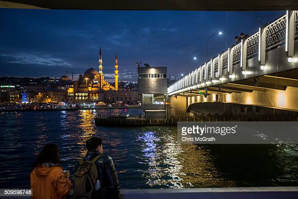 Tourists take in the view of the Eminonu Mosque on February 11 2016 in Istanbul Turkey Istanbul is famous for its skyline dotted with historic...