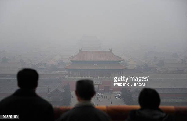 Tourists take in the view of the Forbidden City from atop Coal Hill in Jingshan Park, north of the former imperial palace on a smoggy day in Beijing...