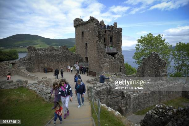Tourists take in Urquhart Castle on the banks of Loch Ness in the Scottish Highlands Scotland on June 10 2018