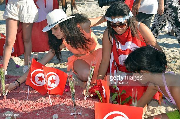 Tourists take part in a gathering in solidarity with Tunisia's tourism industry on June 29 2015 on the island of Djerba following a deadly gun attack...