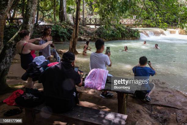 Tourists take photographs and swim in pools at the Kuang Si Waterfall in Luang Prabang Province Laos on Sunday Oct 21 2018 Laos's economy is set to...