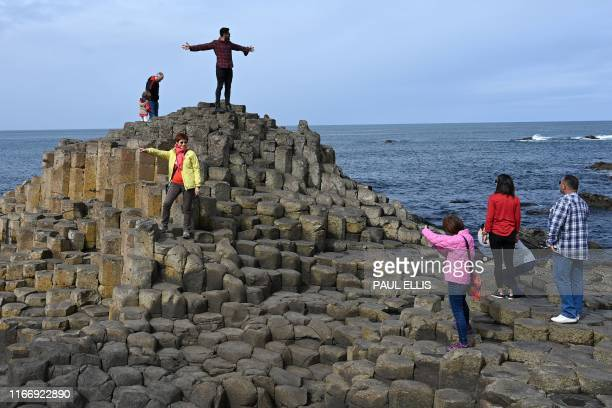 Tourists take photographs as they explore the basalt columns at the Giant's Causeway in Northern Ireland on September 8 2019