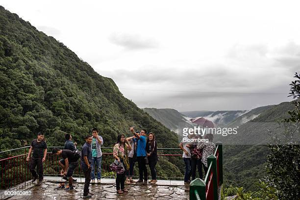 Tourists take photographs at a tourist viewpoint in Cherrapunji Meghalaya India on Saturday Aug 13 2016 Two years of deficient rainfall have affected...