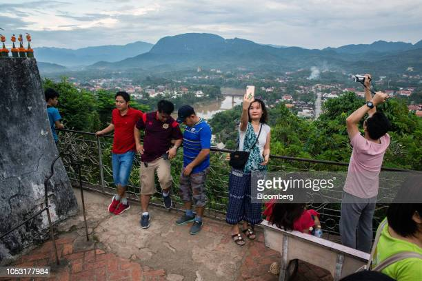 Tourists take photographs at Mount Phousi in Luang Prabang Laos on Sunday Oct 21 2018 Laos's economy is set to expand at 7 percent this year...