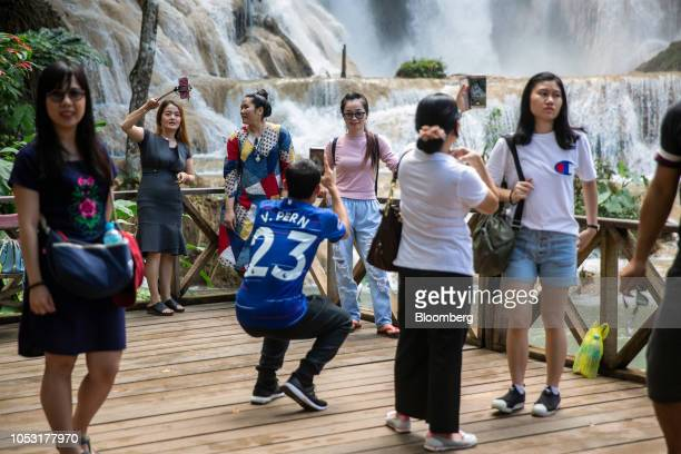 Tourists take photographs at the Kuang Si Waterfall in Luang Prabang Province Laos on Sunday Oct 21 2018 Laos's economy is set to expand at 7 percent...