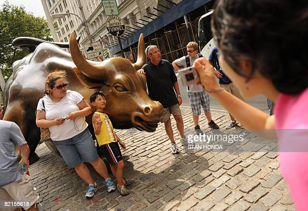 Tourists take photographs by the 'Charging Bull' statue July 31 2008 in the Wall Street area of New York City New York state governor David Paterson...