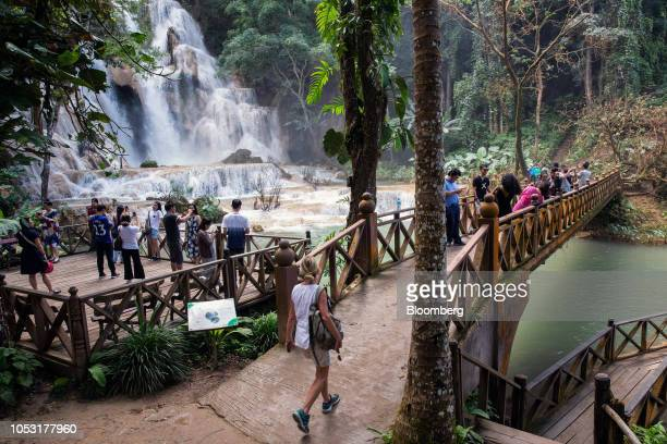 Tourists take photographs from a footbridge and platform at the Kuang Si Waterfall in Luang Prabang Province Laos on Sunday Oct 21 2018 Laos's...