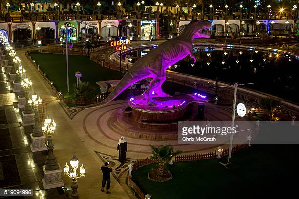 Tourists take photographs in front of a large replica dinosaur at a tourist amusement park on April 2 2016 in Sharm El Sheikh Egypt Prior to the Arab...