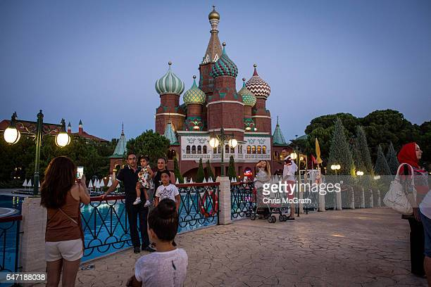 Tourists take photographs in front of a replica of Russia's St Basil's Cathedral at a Russian themed resort on July 11 2016 in Antalya Turkey Russian...