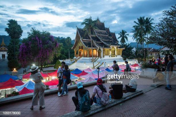 Tourists take photographs in front of the Royal Palace in Luang Prabang Laos on Sunday Oct 21 2018 Laos's economy is set to expand at 7 percent this...