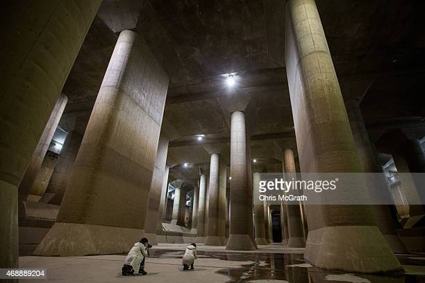Tourists take photographs inside the enormous pressureadjusting underground water tank during a tour of the Metropolitan Area Outer Underground...