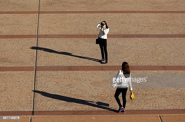 Tourists take photographs near the Sydney Opera House in Sydney Australia on Tuesday July 21 2015 Tired hotels outdated attractions like Sydney's...