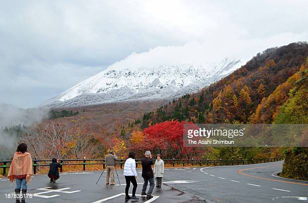 Tourists take photographs of Mt. Daisen, which is covered with the first snow of the season at Kagikake Pass on November 12, 2013 in Kofu, Tottori,...