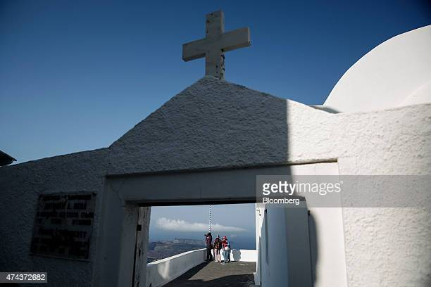Tourists take photographs of the Aegean sea from the yard of a Greek orthodox church in the town of Fira on the island of Santorini Greece on...