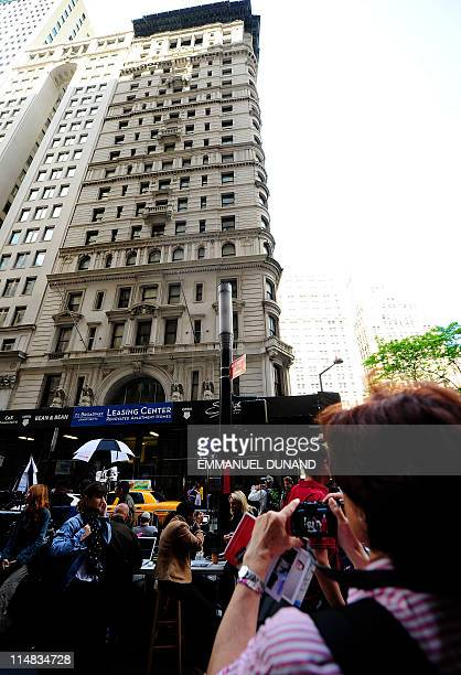 Tourists take photographs of the building where former IMF head Dominique StraussKahn is being held under house arrest after posting bail in New York...