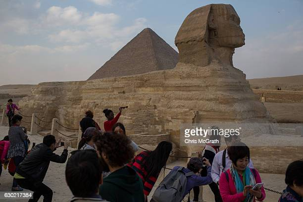 Tourists take photographs of the Great Sphinx of Giza on December 18 2016 in Cairo Egypt Since the 2011 Arab Spring and continued terrorist attacks...