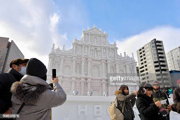 Tourists take photographs of the snow statue of the Ruins of St Paul's in Macau as the 67th Sapporo Snow Festival begins on February 5 2016 in...