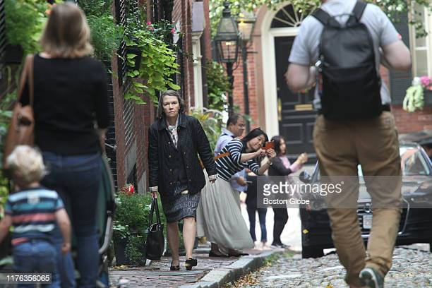Tourists take photographs on Acorn Street in Boston as a woman who entered one of the residences passes through them on the sidewalk on Oct 7 2019...