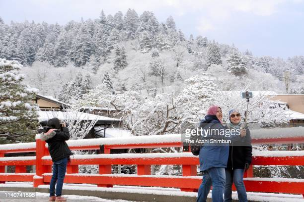 Tourists take photographs snowscapes on Nakabashi bridge on April 3, 2019 in Takayama, Gifu, Japan.