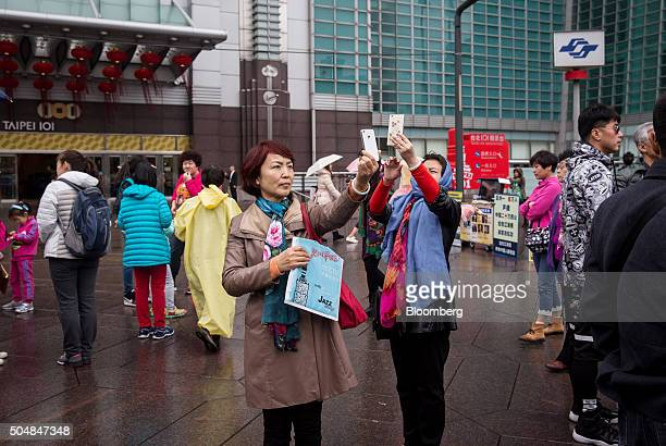 Tourists take photographs using smartphones outside the Taipei 101 building in Taipei Taiwan on Wednesday Jan 13 2016 As many as 188 million voters...