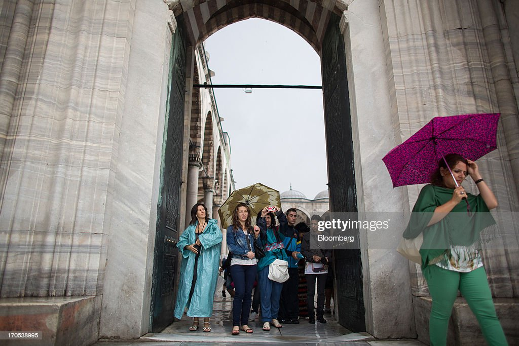 Tourists take photographs while sheltering from the rain in a doorway at the Blue Mosque, also known as the Sultan Ahmed, in Istanbul, Turkey, on Friday, June 14, 2013. The law forbids the sale of alcohol at night and near schools and mosques, going against the secular traditions of the Muslim-majority country of 74 million, where many people drink and women often choose not to cover their hair. Photographer: Lam Yik Fei/Bloomberg via Getty Images